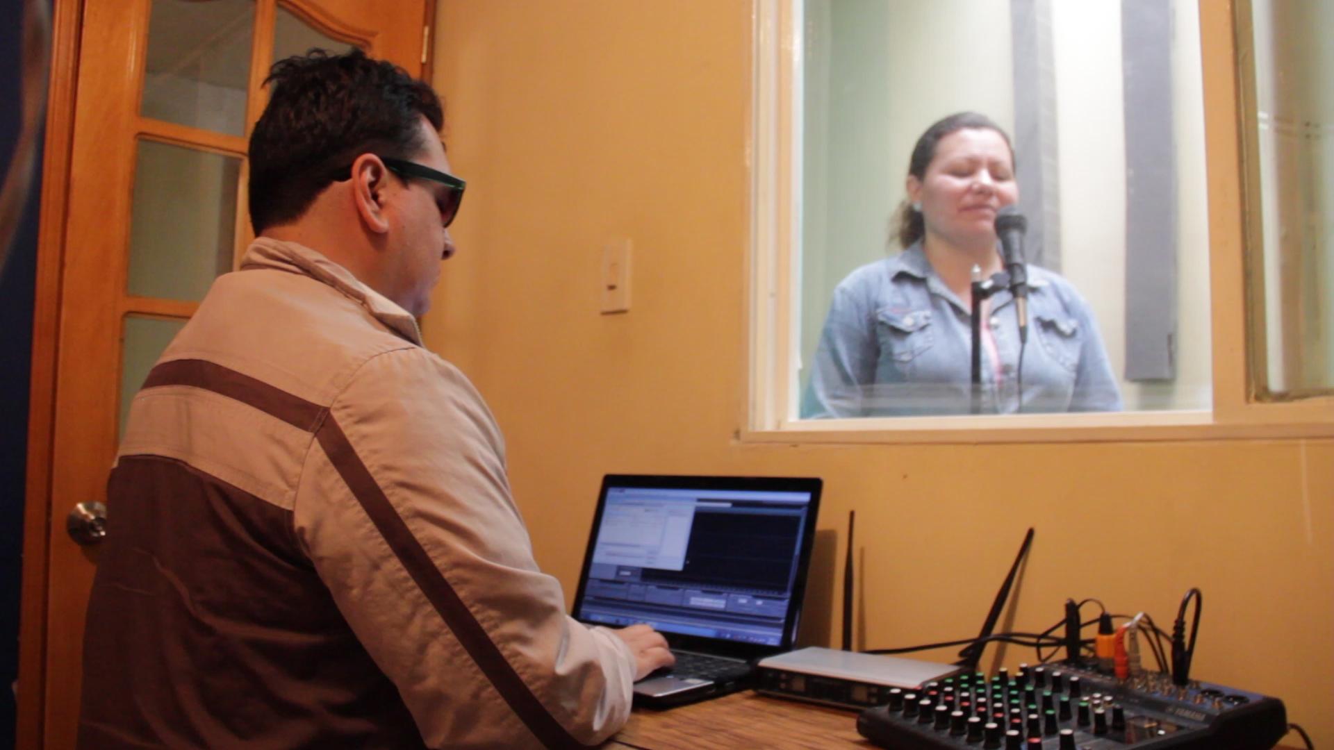 Dos personas transmitiendo en la cabina de Planeta Radio